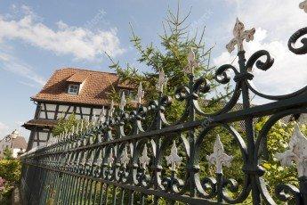 Grille en fer forgé en Alsace avec une maison à colombages