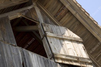 Vieille maison en bois avec un volet battant