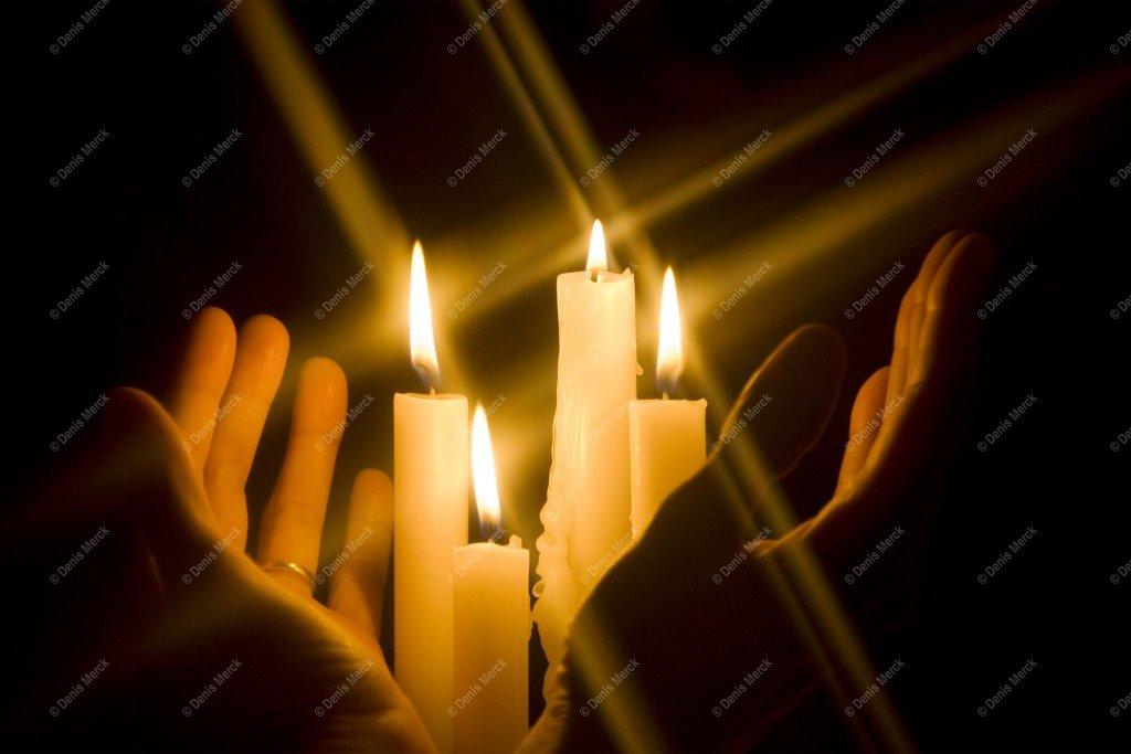 Mains qui entourent des bougies