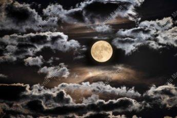 Pleine lune brille sur un ciel nuageux une nuit d'été